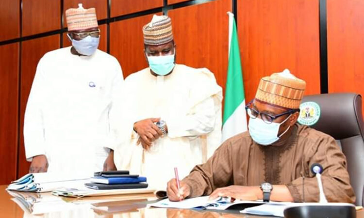 Niger State Governor, Dr. Abubakar Sani Bello Flanked by the Commisioner MWR & DD (L) at the signing of the WASH Corporatization Bill into Law