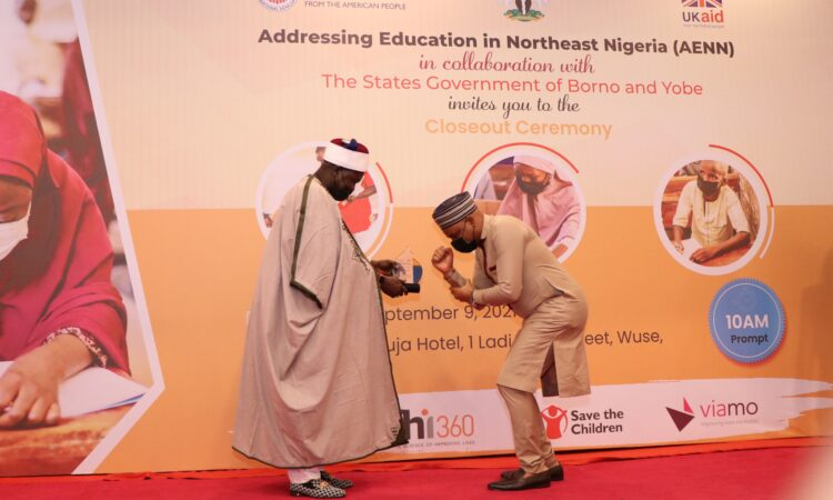 USAID Education Program Manager Olawale Samuel (right) receives an award for his work on the Addressing Education in Northeast Nigeria activity from His Royal Highness Alhaji Mai Abubakar Umar Suleiman, the Emir of Bade, Yobe State (right).