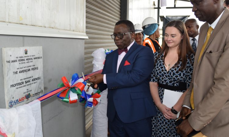 Nigerian Minister of Health Prof. Isaac Adewole (left) cuts the ribbon for a new USAID-supported medical warehouse with USAID Office of Health, Population and Nutrition Director Heather Smith-Taylor (center) and Director of the Ministry's Food and Drug Services Pharmaceutical Division Mashood Lawal (right).
