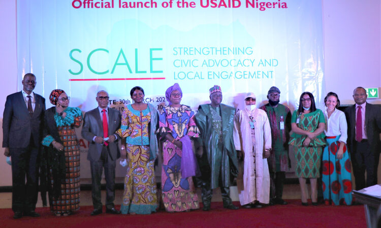 Officials led by Minister of Women Affairs Dame Pauline Tallen (center, pink dress) celebrate the launch of the new USAID Strengthening Civic Advocacy and Local Engagement (SCALE) activity to be implemented in six Nigerian states over the next five years.