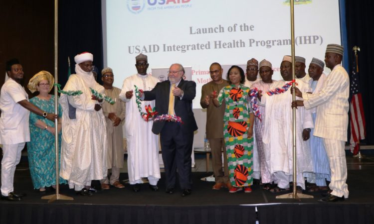 USAID Mission Director Stephen M. Haykin (center) surrounded by health stakeholders cuts a ceremonial ribbon marking the launch of the new $225 million Integrated Health Program which will support primary care in five Nigerian states.
