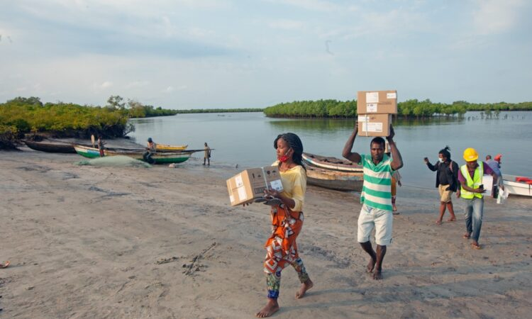 People carrying essential medicines and medical supplies to reach hard-to-reach communities.