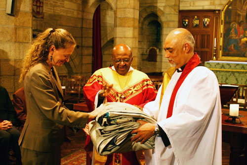Archbishop Tutu (c) blesses the quilt panel as Cathedral Dean Rev. Michael Weeder (r) delivers it to U.S. Consul General Erica Barks-Ruggles