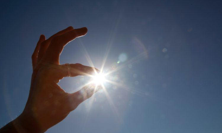 Hand appearing to hold sun between thumb and index finger (© Design Pics via AP)