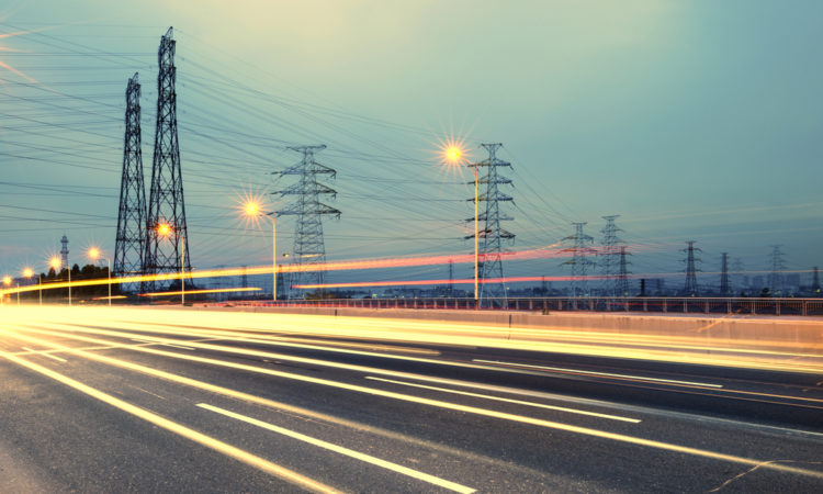 Artistic rendering of power transmission lines with highway lights in foreground (© Shutterstock)