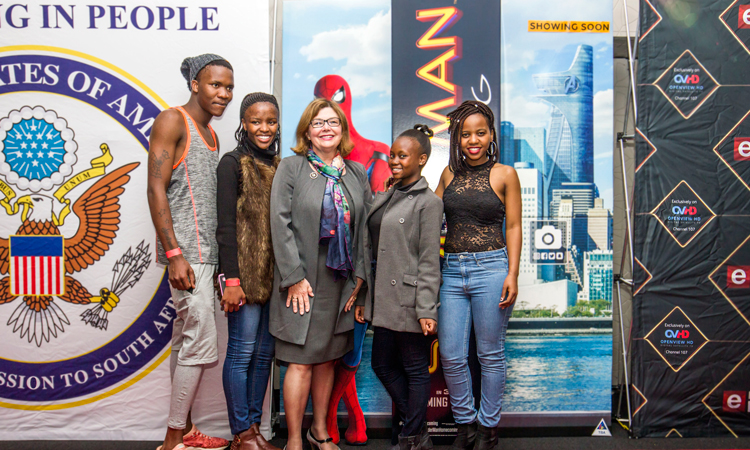 """Five finalists of the """"Hometown Heroes"""" competition on stage with Acting Deputy Chief of Mission Elizabeth McKay, where they received recognition for their community development initiatives and small cash prizes toward the continuation of their work to build their communities."""
