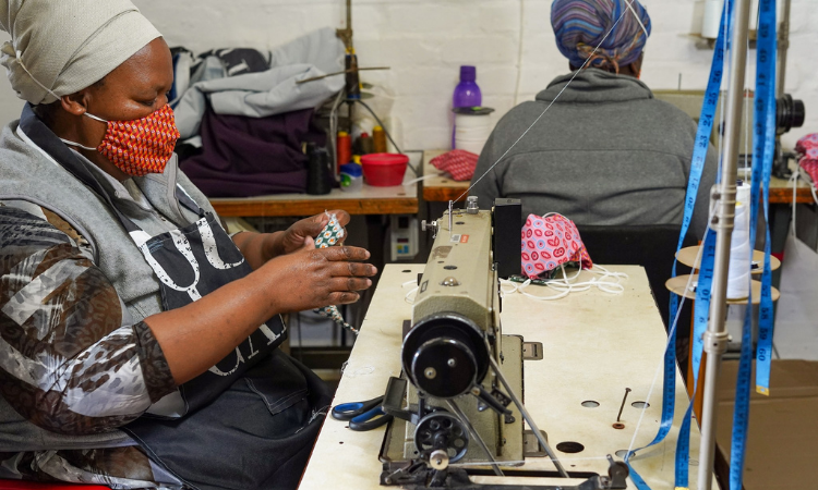Nozibele Stemela, a seamstress at Sakhulwazi Women's Hub in Philippi, Cape Town, South Africa assembles a non-medical, 3-ply fabric face mask to international standards funded in part by a partnership between USAID and the British High Commission in South Africa to spark local production of personal protective equipment.