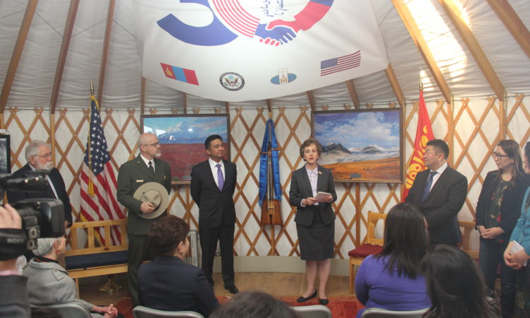 U.S. and Mongolian officials stand before an audience in a ger.