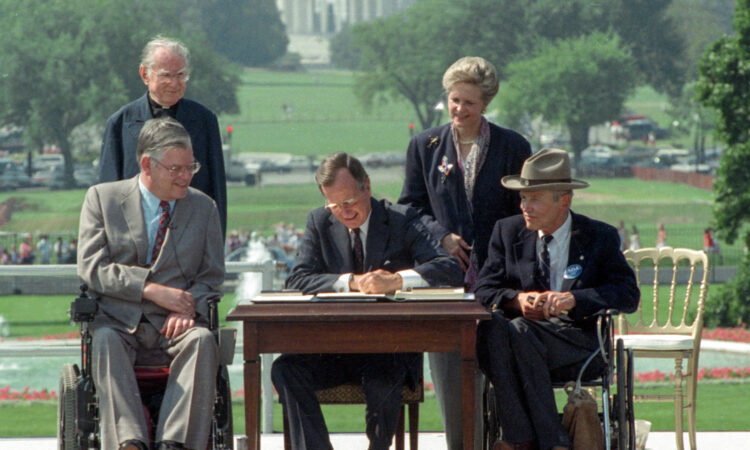 FILE - In this July 26, 1990 file photo, President George H. W. Bush signs the Americans with Disabilities Act during a ceremony on the South Lawn of the White House. Joining the president are, from left, Evan Kemp, chairman of the Equal Opportunity Employment Commission; Rev. Harold Wilke; Sandra Parrino, chairman of the National Council on Disability, and Justin Dart, chairman of The President's Council on Disabilities. TheAmericans with Disabilities Act, which was signed into law 25 years ago, on July 26, 1990. (© Barry Thumma/AP Images)