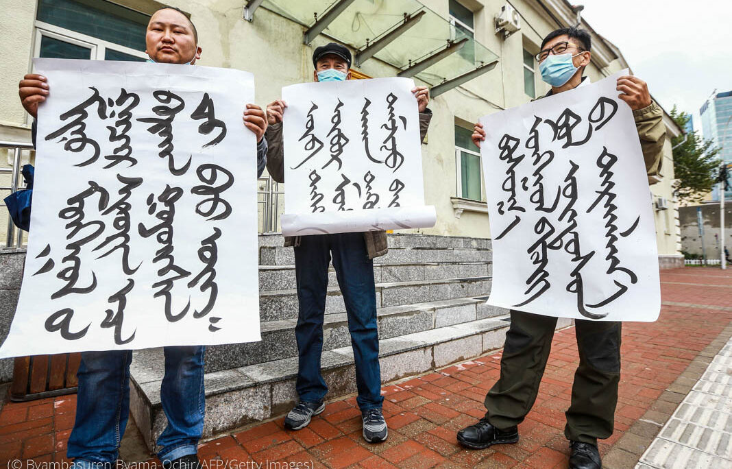 Three people holding up signs written in Mongolian. (© Byambasuren Byamba-Ochir/AFP/Getty Images)