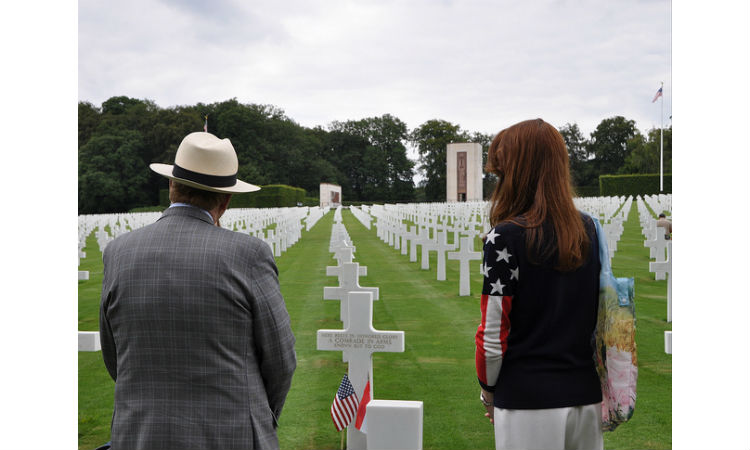Man and woman standing in cemetary. (Embassy Image)