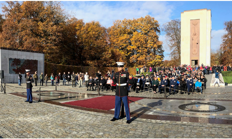 Servicemember and audience outside memorial. (Embassy Image)