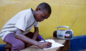 Zambian youth completes schoolwork while listening to radio.
