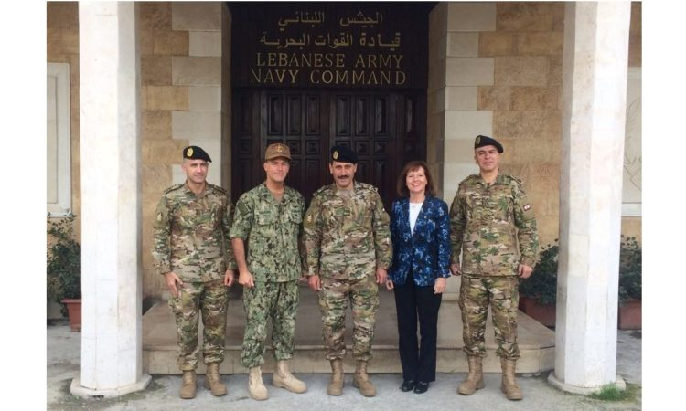 Four military men and woman standing in front of a building