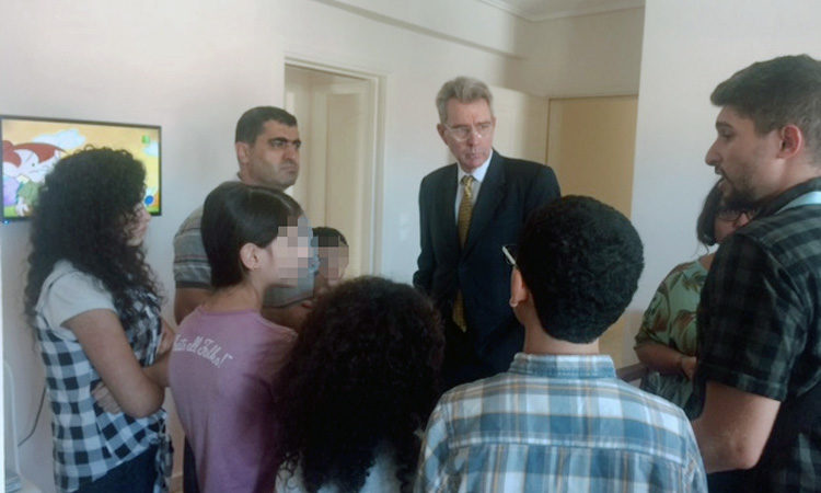 Ambassador Pyatt discusses with refugee family in Livadia (State Department Photo)