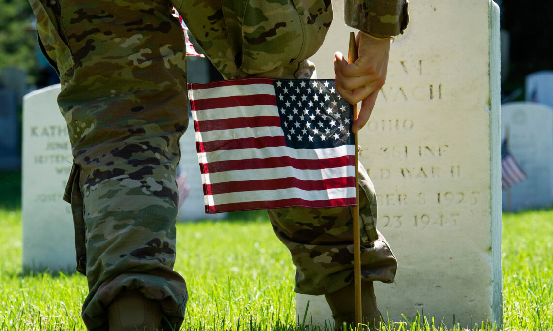 """A member of the Army's 3rd U.S. Infantry Regiment, a unit known as the Old Guard, places a flag at the headstone of a fallen military member during the unit's annual Memorial Day """"Flags In"""" ceremony at Arlington National Cemetery in Arlington, Virginia."""