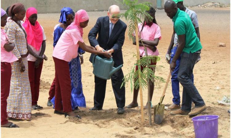 L'Ambassadeur Zumwalt aide une élève du lycée Kennedy à planter un arbre.