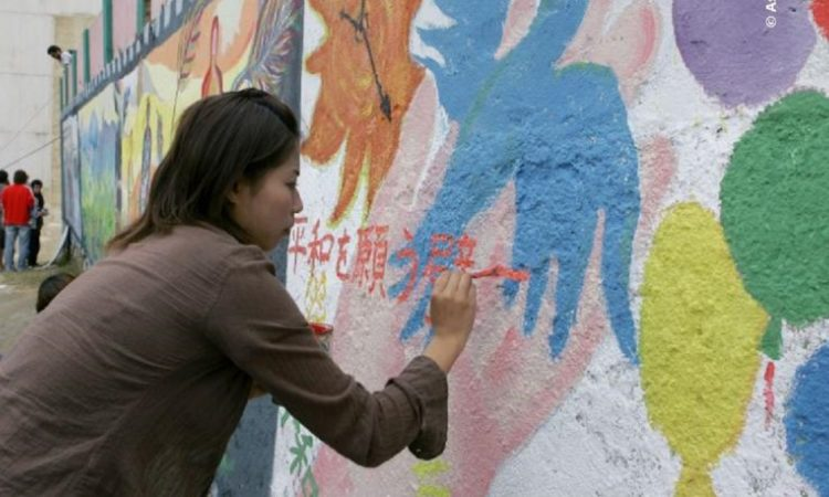Eine Frau malt ein Friedensbild an eine Wand.