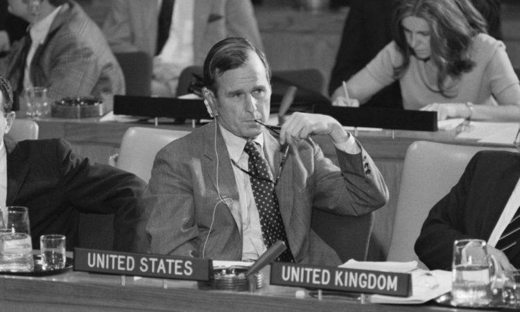 """George H. W. Bush am Tisch, vor ihm ein Schild mit der Aufschrift """"Vereinigte Staaten"""" (Foto: Getty Images)"""