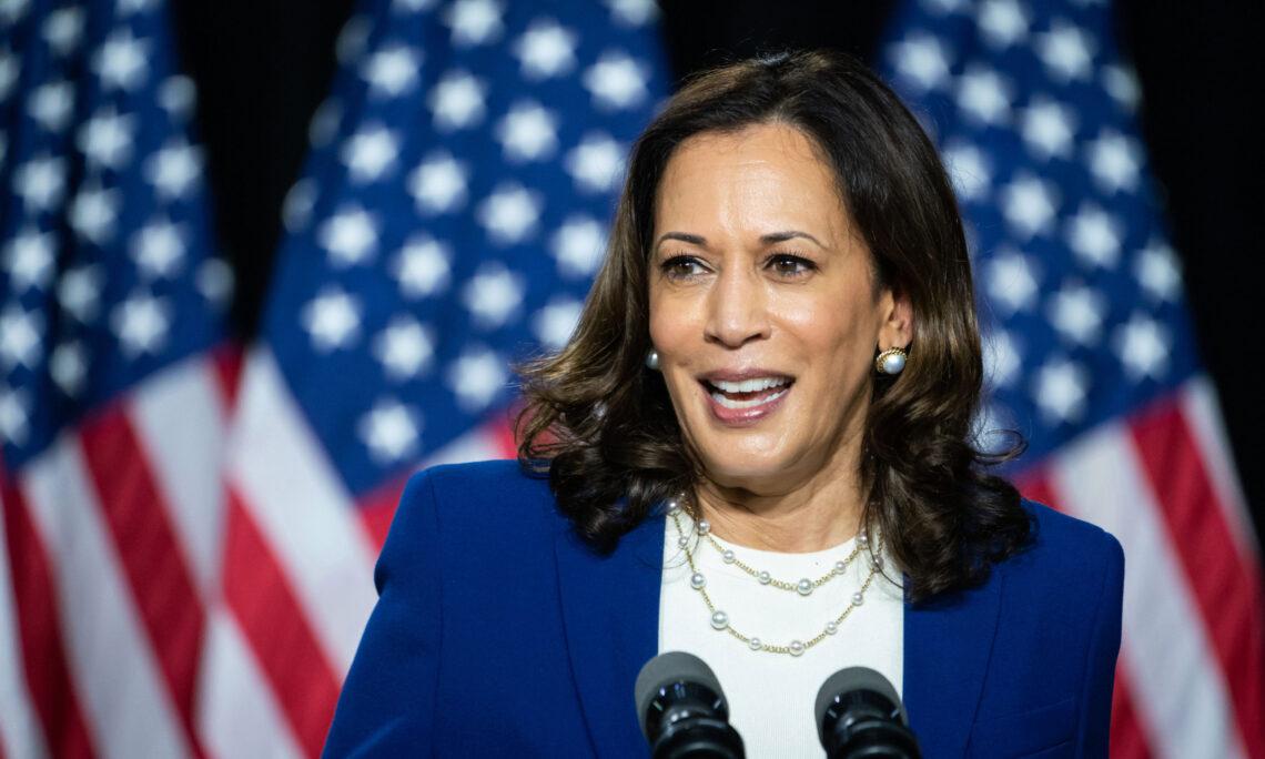 Vizepräsidentin Harris in einem blauen Blazer vor drei amerikanischen Flaggen, als sie ihre Kandidatur für das Amt der Vizepräsidenten in Wilmington (Delaware) bekannt gibt