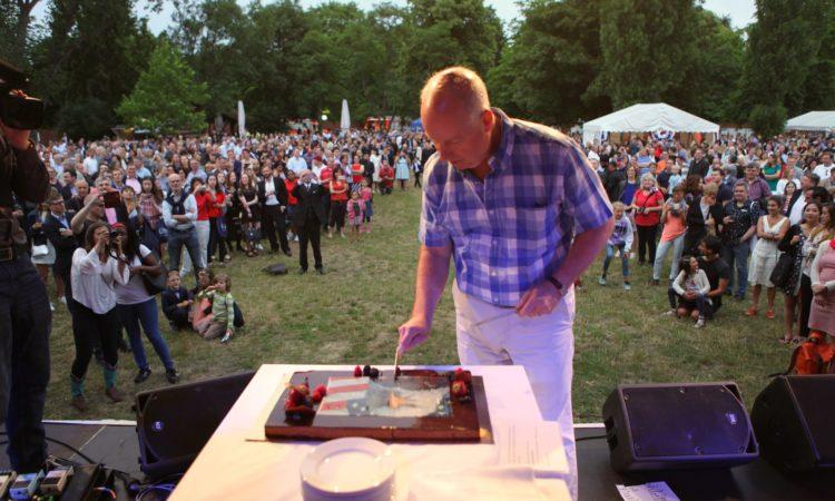 Chargé d'Affaires Logsdon cutting the birthday cake