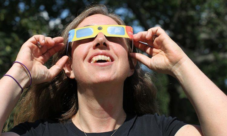 Eine Frau beobachtet die Sonnenfinsternis durch eine spezielle Schutzbrille (Foto: Boston Globe via Getty Images)