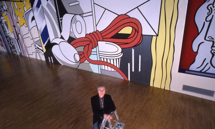 Ein Mann auf einer Leiter schaut nach oben, hinter ihm ein großes, buntes Gemälde. (Foto: Estate of Roy Lichtenstein, Michael Abramson)