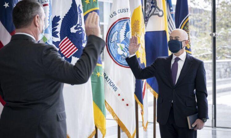 Zwei Männer stehen sich mit Maske gegenüber und heben die rechte Hand zum Eid