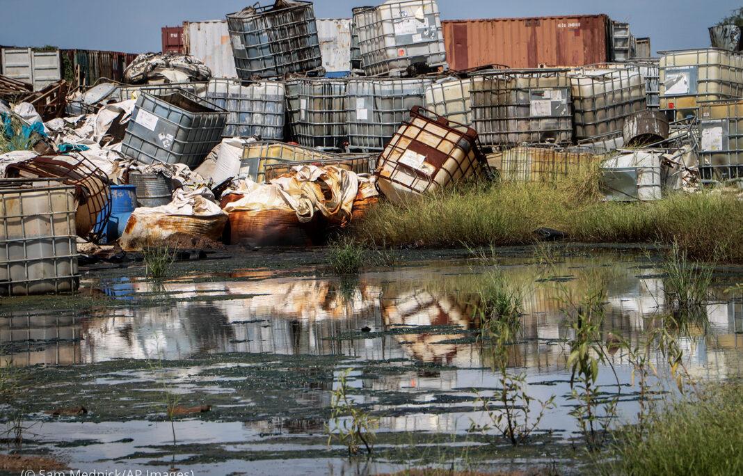 Behälter mit         gefährlichem Sondermüll stapeln sich in Wassernähe. (Foto: Sam         Mednick/AP Images)