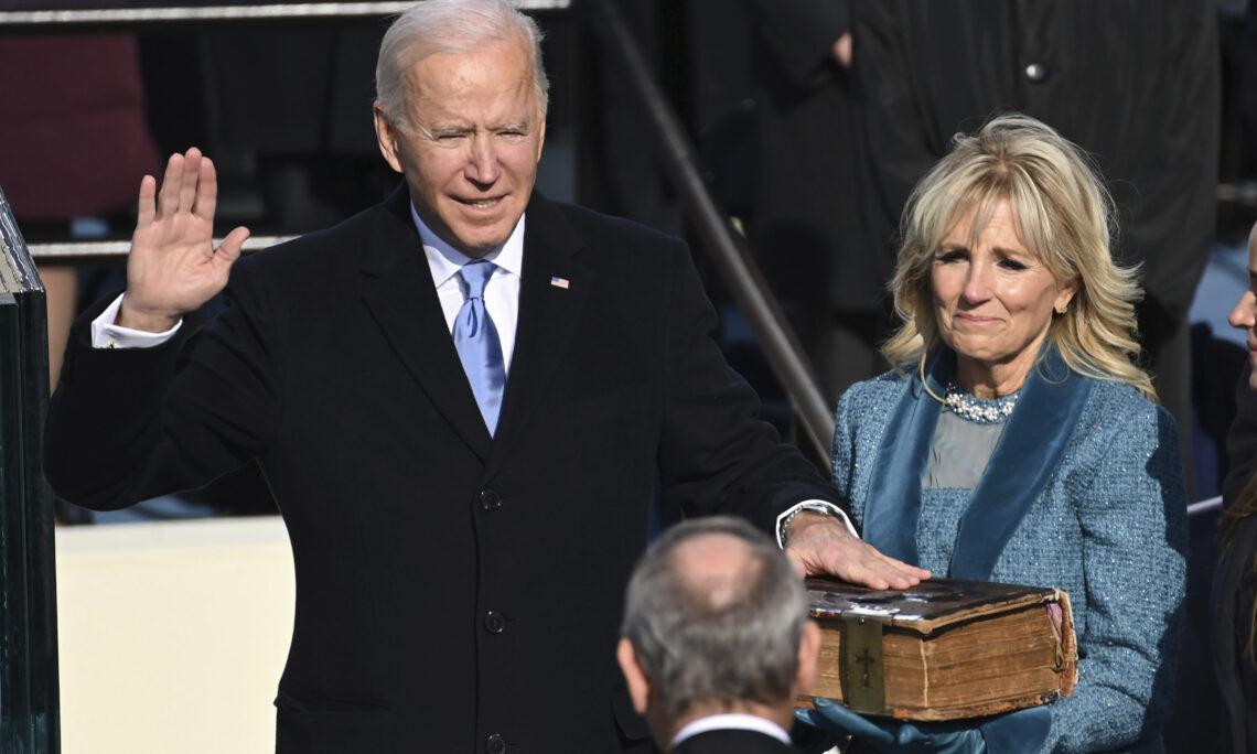 Joe Biden hebt die rechte Hand zum Eid, die linke ruht auf der Bibel. Neben ihm steht seine Ehefrau Jill.