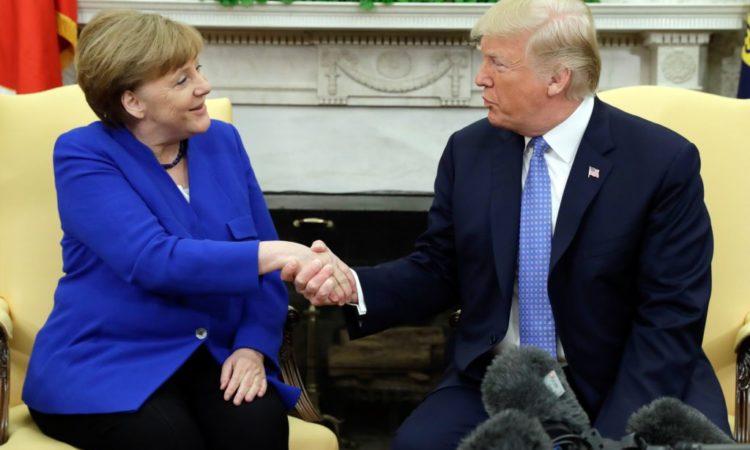 Angela Merkel und Donald Trump sitzen und schütteln sich die Hände (Foto: Evan Vucci/AP Images)