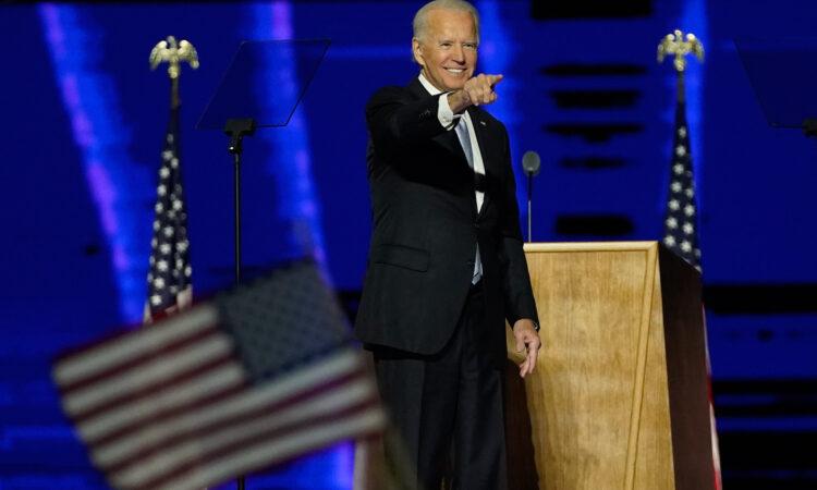 Joe Biden zeigt von einer Bühne aus ins Publikum, im Vordergrund eine US-Flagge