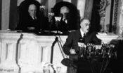 Franklin Delano Roosevelt am Rednerpult mit Mikrofonen. Hinter ihm sitzen zwei Männer. (Foto: AP Images)