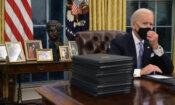 US-Präsident Biden an seinem Schreibtisch, eine Hand an seiner Maske, auf einem Tisch¬ im Hintergrund die Büste von César Chávez und einige gerahmte Bilder.