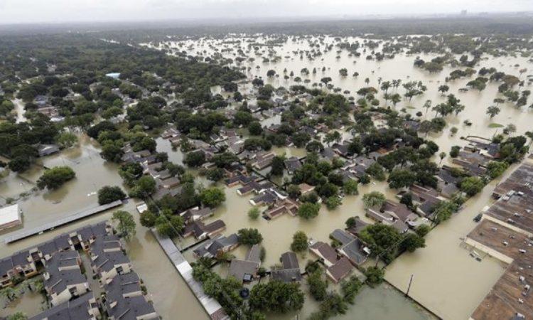 Luftansicht eines überschwemmten Wohngebiets außerhalb von Houston (Texas) – lediglich die Baumkronen und Dächer ragen noch aus dem Wasser.