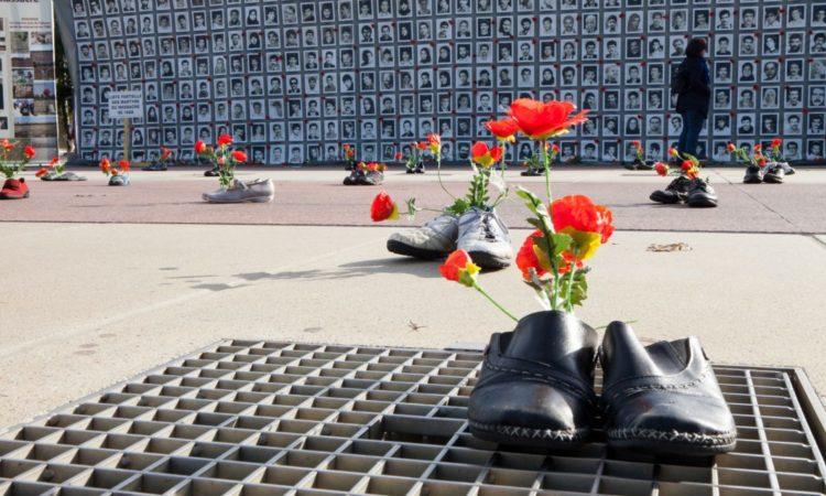 Auf einem Gitterrost stehen ein Paar Schuhe, in dem rote Blumen stecken (Foto: Siavosh Hosseini/NurPhoto/Getty Images)