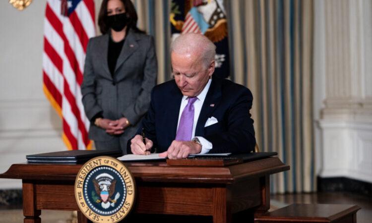 Präsident Biden unterzeichnet Schriftstücke, während Vizepräsidentin Harris ihm zusieht