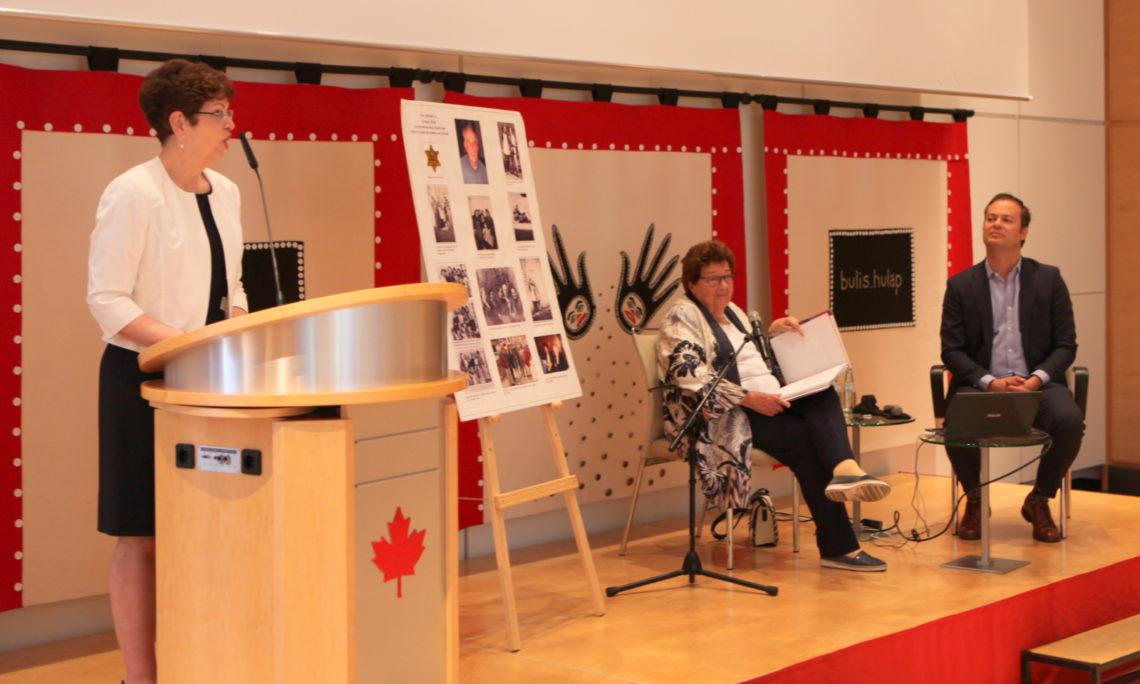 Rednerin auf Bühne mit zwei sitzenden Zuhörern