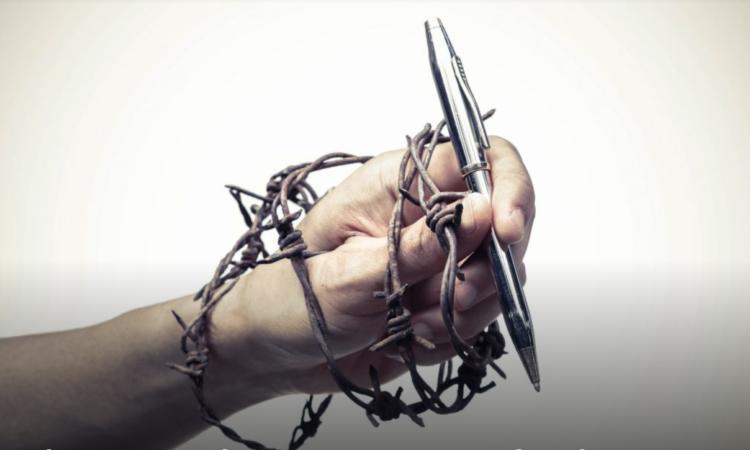Hand, umwickelt mit Stacheldraht, hält Stift (Foto: Shutterstock)