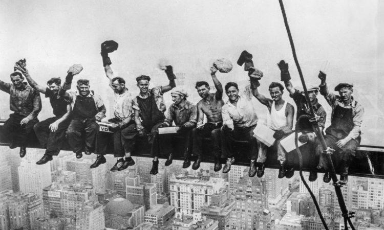 Bauarbeiter sitzen auf einem Tragbalken hoch über einer Stadt (Foto: Granger)