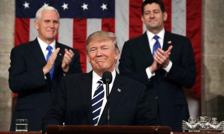 Präsident Trump lächelnd am Rednerpult, hinter ihm zwei Amtsträger, die applaudieren. (Foto: AP Images)