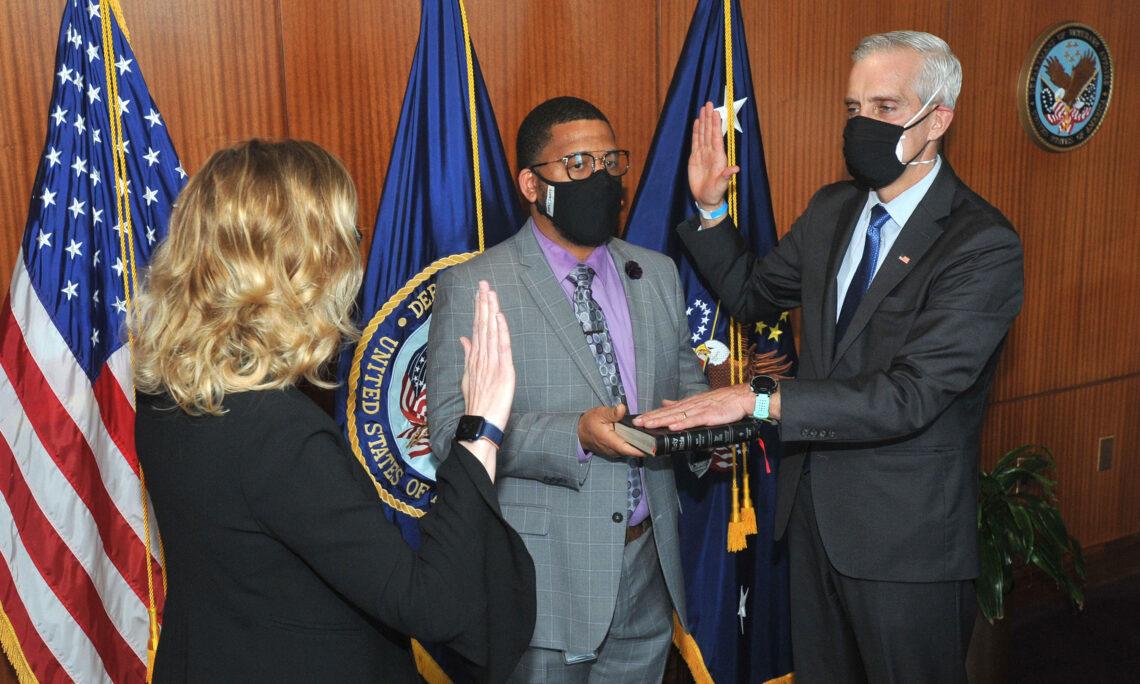 Denis R. McDonough steht mit zwei weiteren Personen vor drei amerikanischen Flaggen, eine Hand zum Eid erhobenen und die andere auf einer Bibel ruhend
