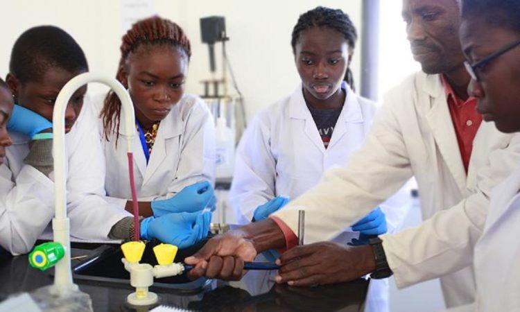Mädchen stehen im Labor am Tisch und sehen bei einen Experiment zu