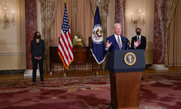 US-Präsident Biden am Podium, hinter ihm US-Vizepräsidentin Kamala Harris und US-Außenminister Antony Blinken neben Flagggen