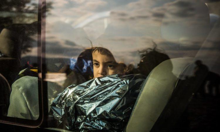 Ein in eine Rettungsdecke gewickelter Junge – einer von Tausenden, die vor der Gewalt in Syrien geflohen sind – schaut auf der griechischen Insel Lesbos im Dezember 2015 aus dem Fenster eines Busses. (Foto: AP Images)