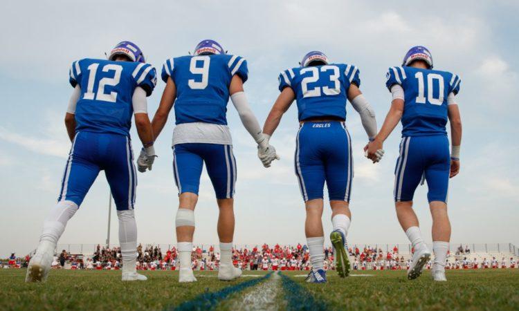 Football-Spieler von hinten halten sich an den Händen (Foto: Tim Richardson)