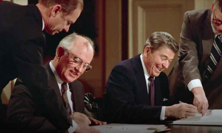 Zwei Männer zeigen Michail Gorbatschow und Ronald Reagan wo sie den Vertrag unterzeichnen sollen. (Foto: Bettmann/Getty Images)