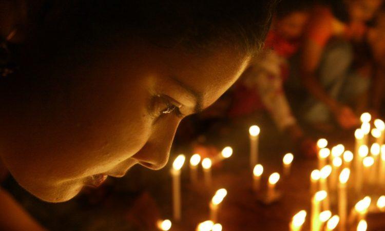Während einer Mahnwache: Frau blickt auf brennende Kerzen (Foto: AP Images)