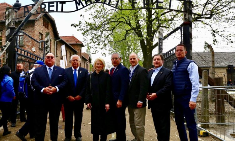 Seven adults standing below the Arbeit macht frei gate