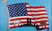 Amerikanische Flagge mit Abbildung von Rindern, die das Volk der Massai nach dem 11. September den Amerikanerinnen und Amerikanern schenkte. (Foto: Matt Flynn/9/11 Memorial Museum/Geschenk von Wilson Kimeli Naiyomah und dem Volk der Massai in Kenia)
